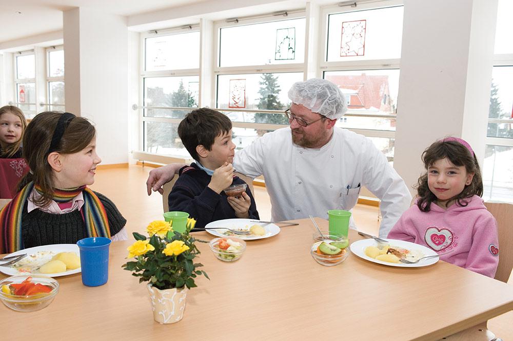 Der Koch spricht mit zwei Mädchen und einem Jungen am Mittagstisch.