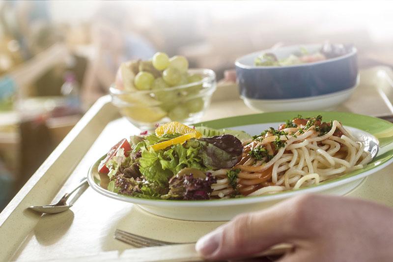 Ein Essenstablett mit einem Teller Spagetti, frischem Salat und einer Schale Weintrauben