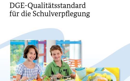 """Titelbild der Broschüre """"DGE-Qualitätsstandard für Schulverpflegung. Zu sehen sind ein Mädchen und ein Junge lachend am Mittagstisch."""