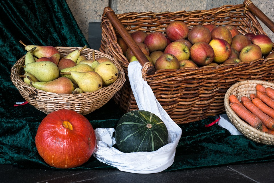 Foto mit drei Körben voller Birnen, Äpfeln und Möhren. Davor ein roter und ein grüner Kürbis.
