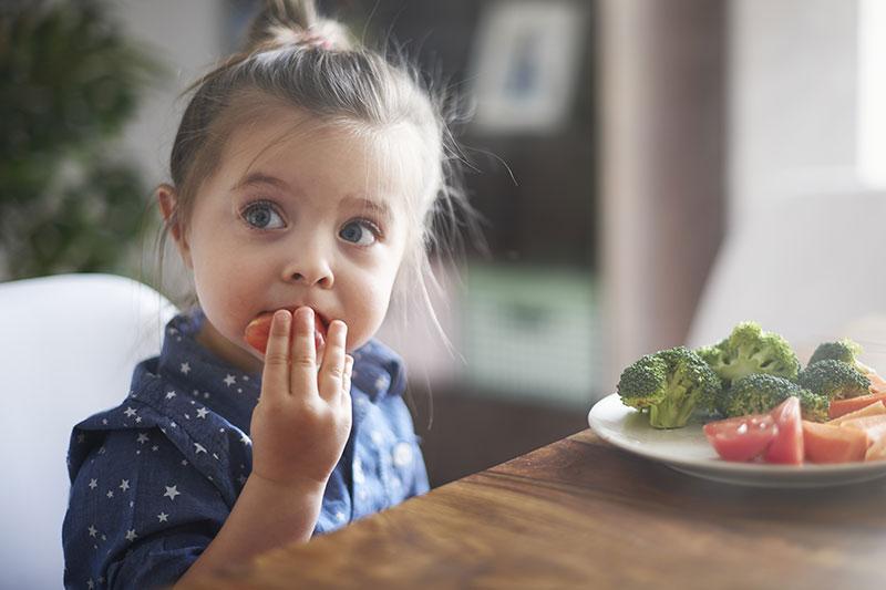 Ein kleines braunhaariges Mädchen sitzt vor einem Teller mit Tomaten und Brokkoli und isst eine Tomate