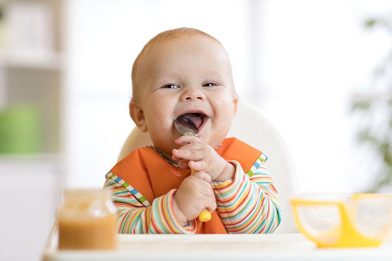 Lachendes Baby mit Löffel in der Hand