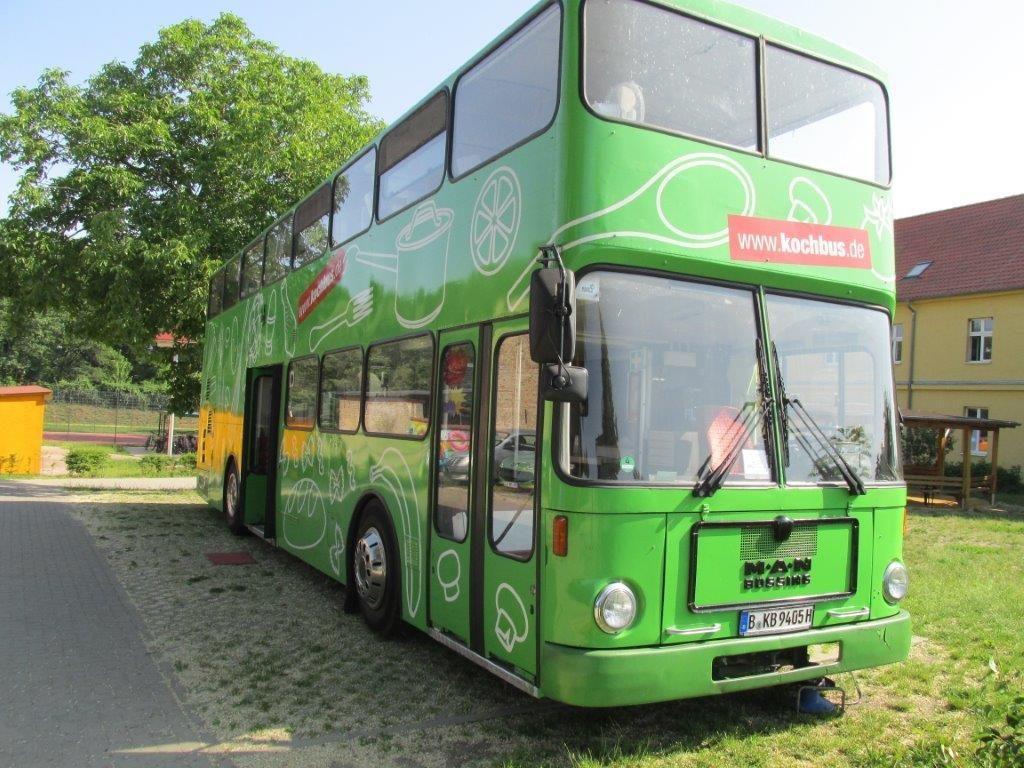 Der grüne Kochbus steht bei sommerlichem Wetter auf dem Gelände der Grundschule Jeserig